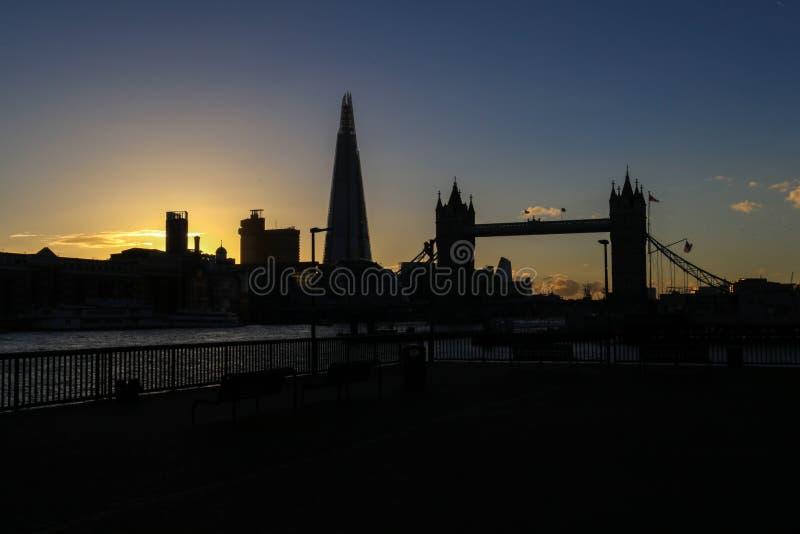 Изумительный заход солнца в Лондоне против фона моста башни и черепка стоковые фотографии rf