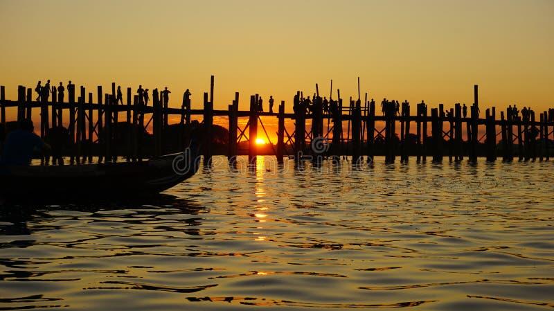 Изумительный заход солнца через деревянный мост в Мандалае стоковые фотографии rf