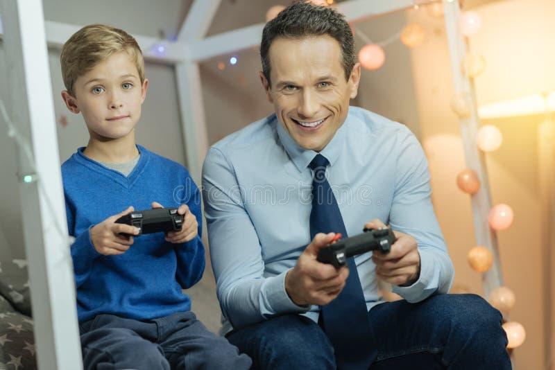 Изумительный мальчик играя игры с его папой стоковое изображение