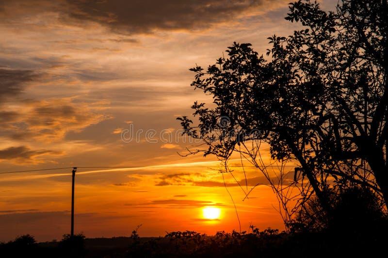 Изумительный сельский красный заход солнца в свете последнего вечера стоковое изображение