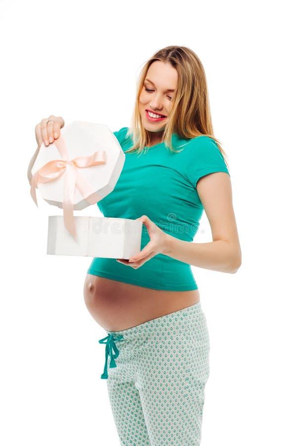 Изумительная беременная женщина держа коробку с смычком подарок, раскрывает подарок, счастливые эмоции студия, белая предпосылка стоковые фото