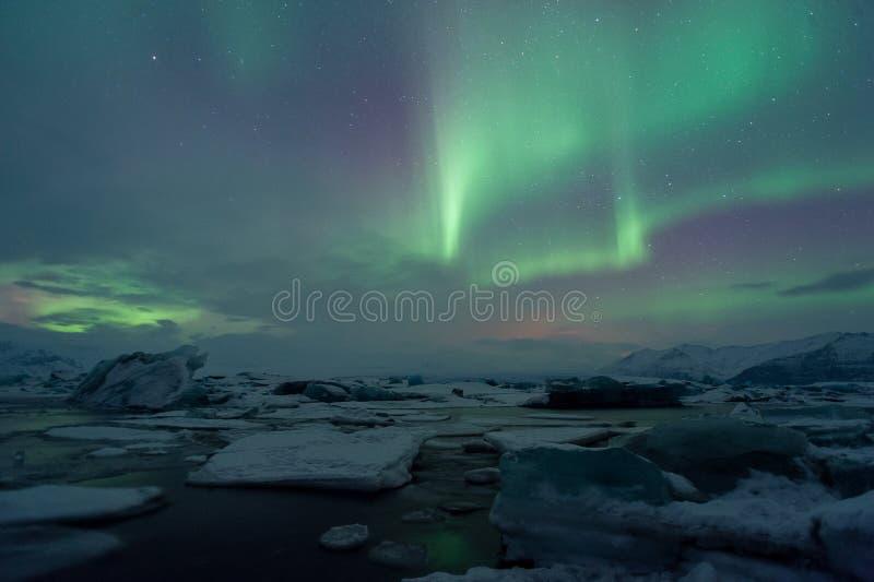 Изумительное северное сияние над лагуной ледника в зиме Исландии стоковые фото