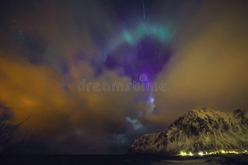 Изумительные пестротканые северные сияния также знают по мере того как северное сияние в ночном небе над ландшафтом Lofoten, Норв стоковые изображения