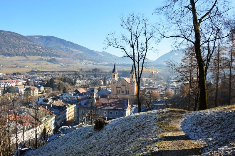 Изумительный взгляд зимы Brunico с церковью в середине изображения, Bruneck Santa Maria Assunta, Италией стоковая фотография