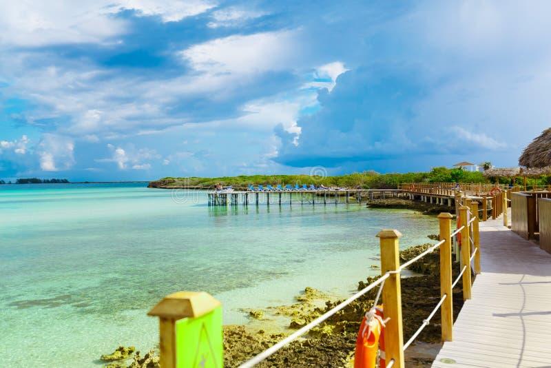 Изумительный взгляд от палубы пристани пляжа на спокойном океане и пасмурного голубого неба при люди ослабляя в предпосылке стоковое изображение