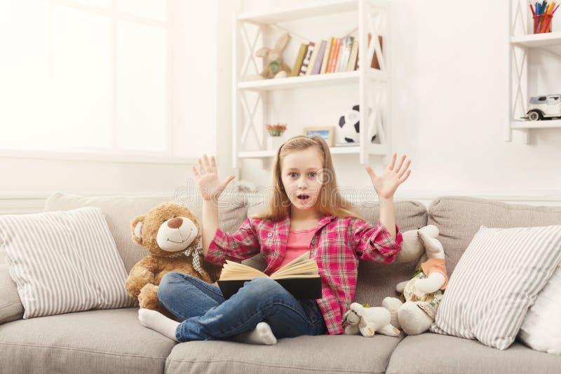 Изумленная маленькая девочка с книгой и ее любимыми игрушками дома стоковое изображение rf