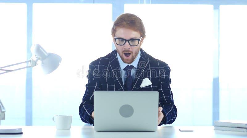 Изумленный бизнесмен, удивленный человек Redhead работая на компьтер-книжке стоковое фото rf