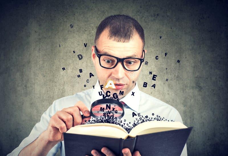Изумленный человек читая книгу с летанием писем далеко от его стоковые изображения rf