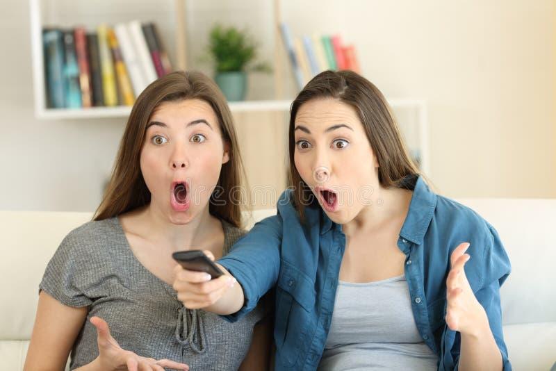 2 изумленных друз смотря ТВ дома стоковое фото rf