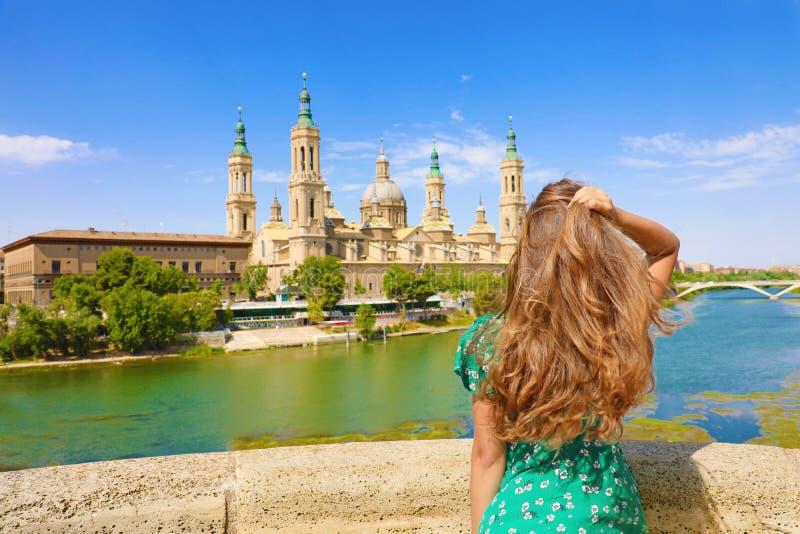 Изумлять назад взгляд привлекательной красивой женщины смотря базилику собора нашей дамы штендера в Сарагосе, Испания стоковые фотографии rf
