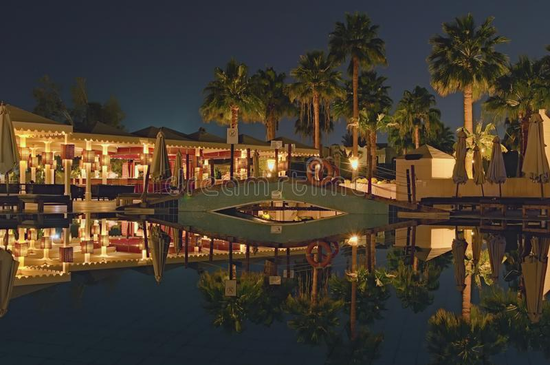 Изумляя взгляд ночи тропического района роскошного отеля с бассейном, пальмой и красивыми освещениями ночи стоковая фотография rf