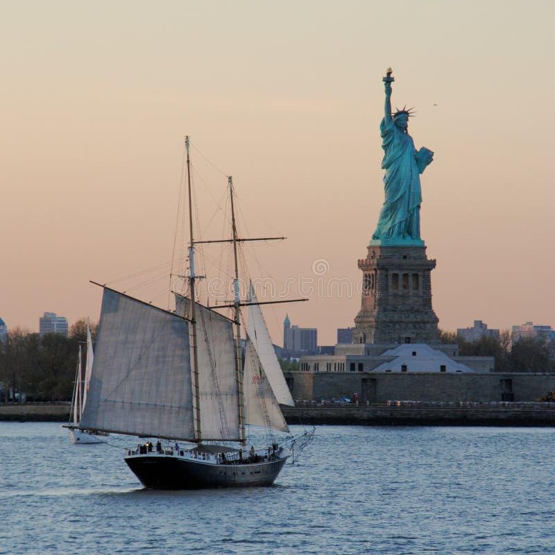 Изумляя взгляд статуи свободы и парусника, на заходе солнца стоковые изображения