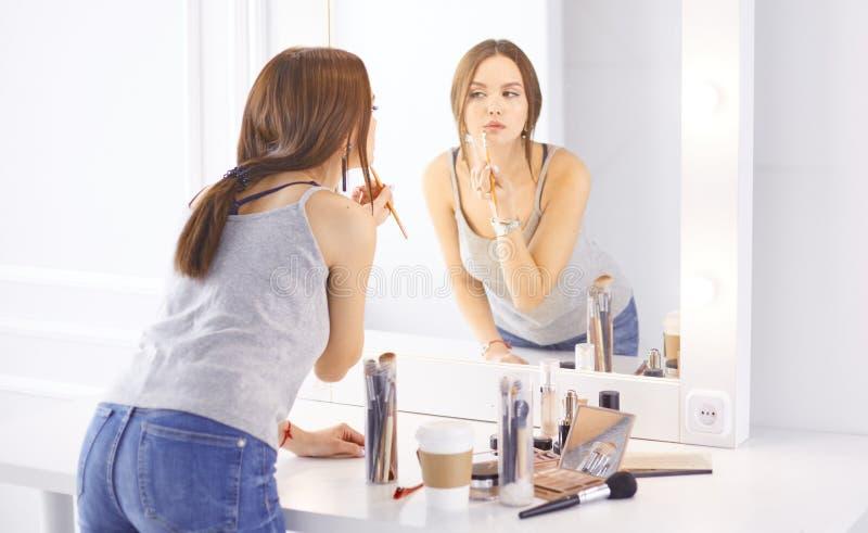 Изумляя молодая женщина делая ее макияж перед зеркалом Портрет красивой девушки около косметической таблицы стоковая фотография rf