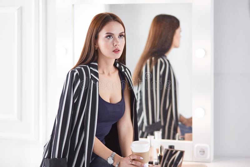Изумляя молодая женщина делая ее макияж перед зеркалом Портрет красивой девушки около косметической таблицы стоковые фото