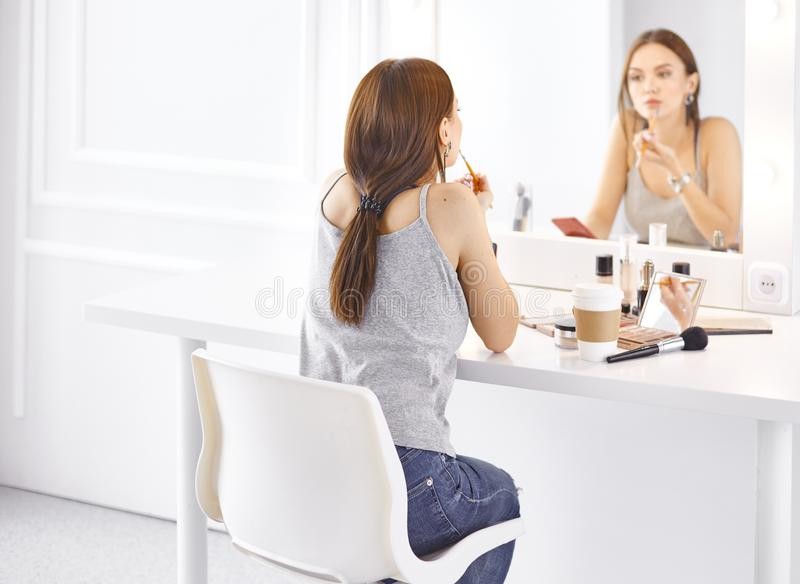 Изумляя молодая женщина делая ее макияж перед зеркалом Портрет красивой девушки около косметической таблицы стоковая фотография