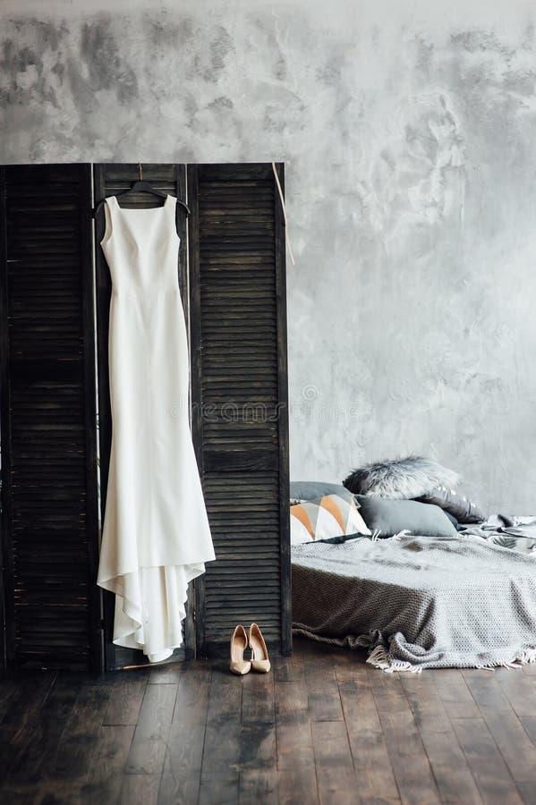 Изумляя платье свадьбы вися на экране около серой кровати в комнате просторной квартиры стоковая фотография rf