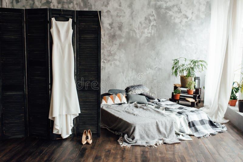 Изумляя платье свадьбы вися на экране около серой кровати в комнате просторной квартиры стоковая фотография