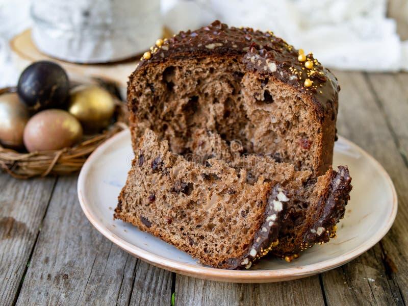 Изумляя торт пасхи шоколада с падениями шоколада и сухие вишни на старой деревянной предпосылке с черными и золотыми яйцами ломти стоковое фото