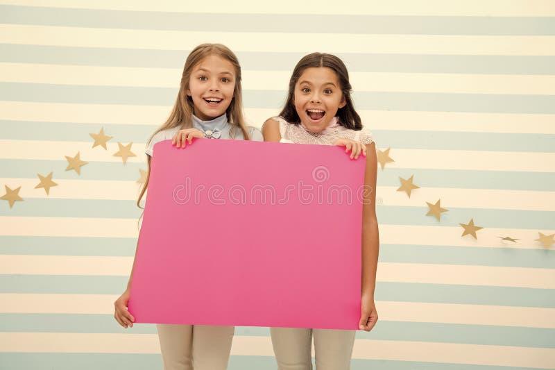 Изумляя удивительные новости Знамя объявления владением девушки Дети девушек держа бумажное знамя для объявления Дети счастливые стоковые изображения