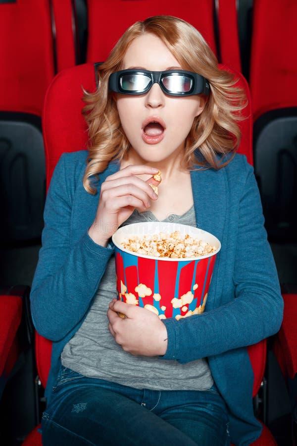 Изумленная женщина в стеклах есть попкорн стоковое изображение