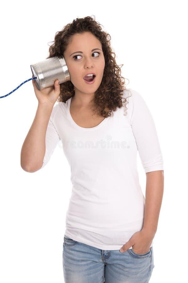 Изумленная и оглушенная изолированная девушка слушая к жестяной коробке стоковые фото