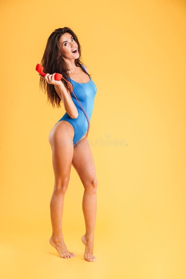 Изумленная курчавая женщина в голубом купальнике говоря на красном телефоне стоковые фото