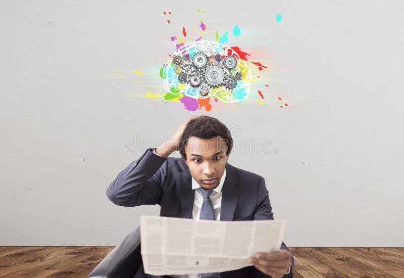 Изумленный африканский бизнесмен, газета, cogs мозга стоковое фото rf