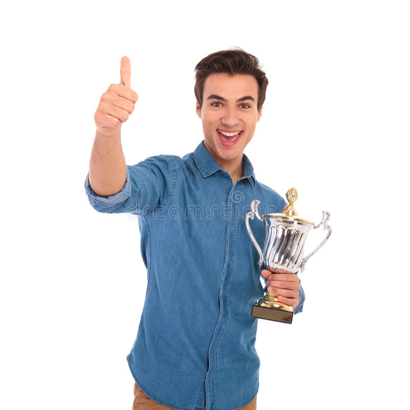 Изумленный человек держа чашку трофея и делает одобренный знак стоковые фотографии rf
