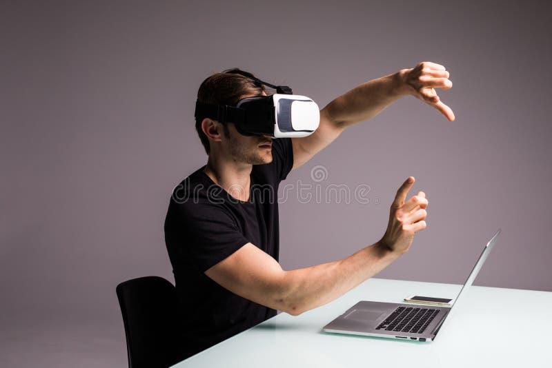 Изумлённые взгляды виртуальной реальности молодого человека нося и видеоигра играть указали с пальцами Концепция игры стоковые фото