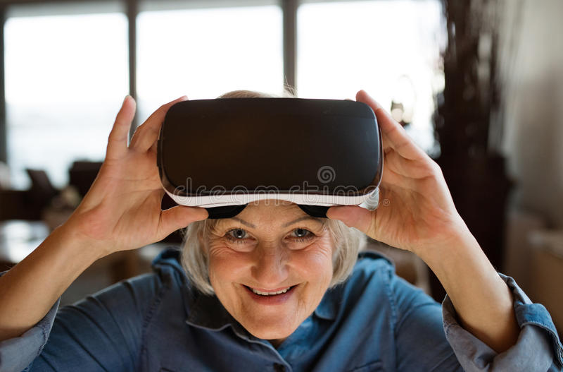 Изумлённые взгляды виртуальной реальности старшей женщины нося дома стоковая фотография rf