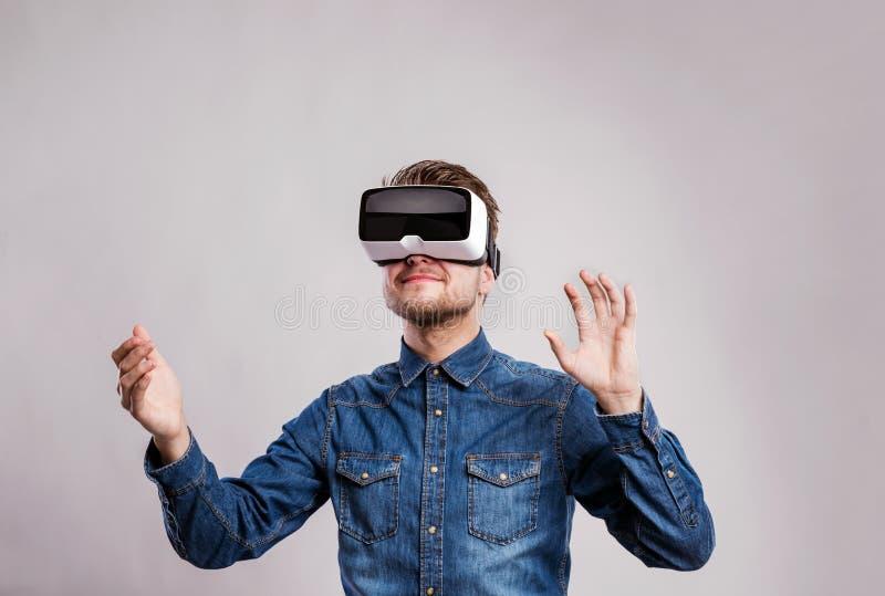 Изумлённые взгляды виртуальной реальности человека нося Съемка студии, серое backgrou стоковое изображение