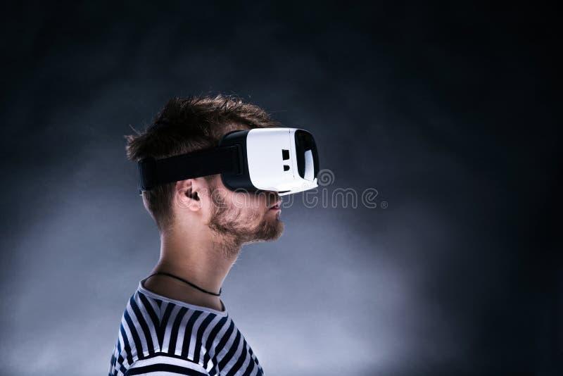 Изумлённые взгляды виртуальной реальности человека нося Съемка студии, черное backgrou стоковое изображение