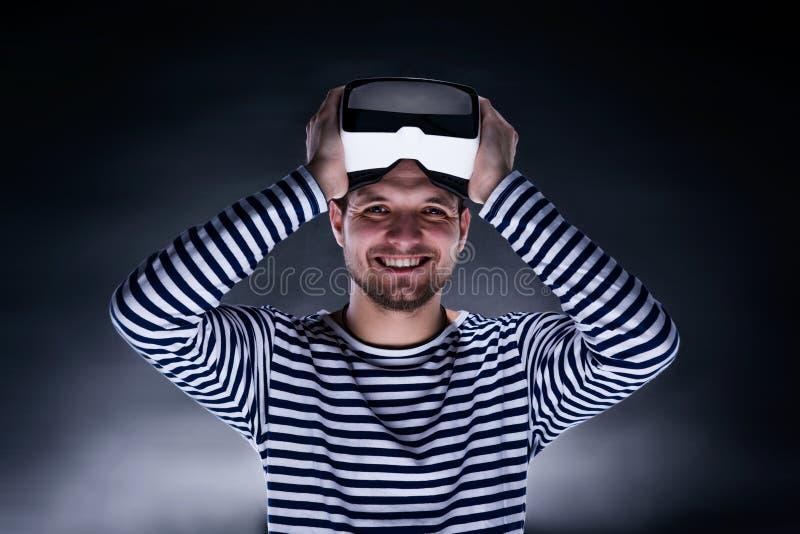 Изумлённые взгляды виртуальной реальности человека нося Съемка студии, черное backgrou стоковые фото