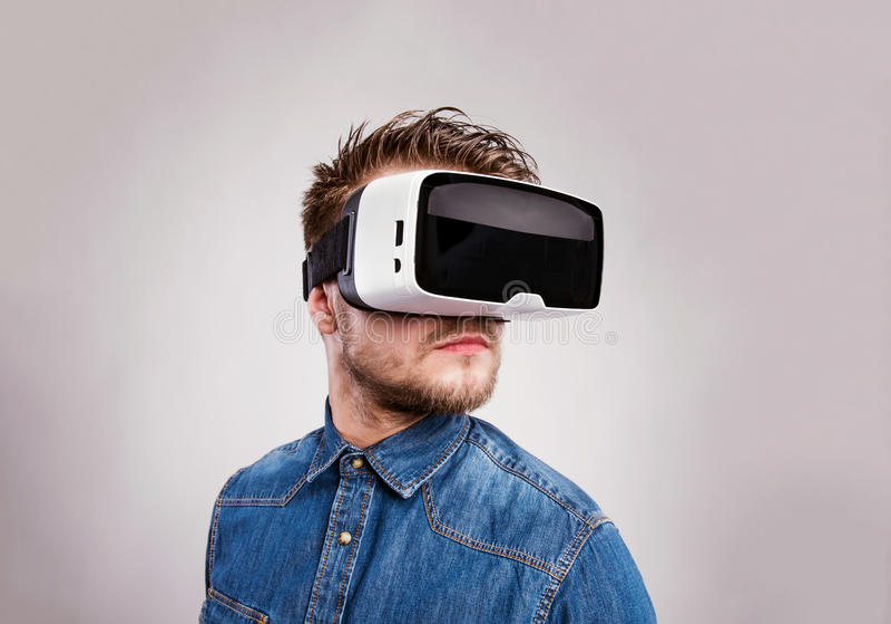 Изумлённые взгляды виртуальной реальности человека нося Съемка студии, серое backgrou стоковое изображение rf