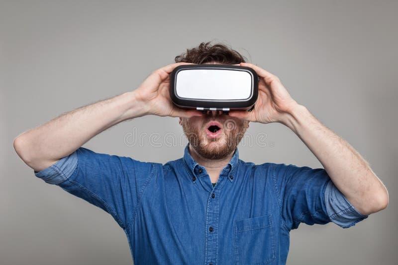 Изумлённые взгляды виртуальной реальности человека нося стоковое изображение rf