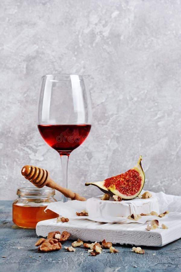 Изысканная закуска белых сыра или камамбера бри со свежими смоквами, гайками, медом и красным вином для пробовать стоковые изображения