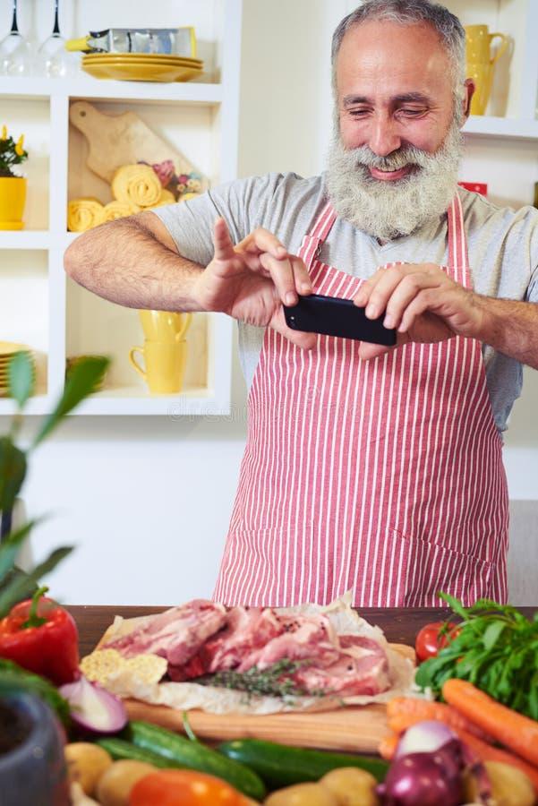 Изысканный шеф-повар принимает фото закалённого мяса для того чтобы делить с друзьями стоковые фото
