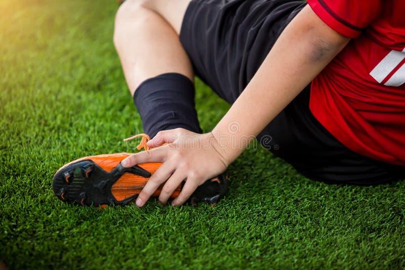 Из-за боли футболист сидит и ловит лодыжку ног, а футболист получил ранение в ногу стоковые изображения