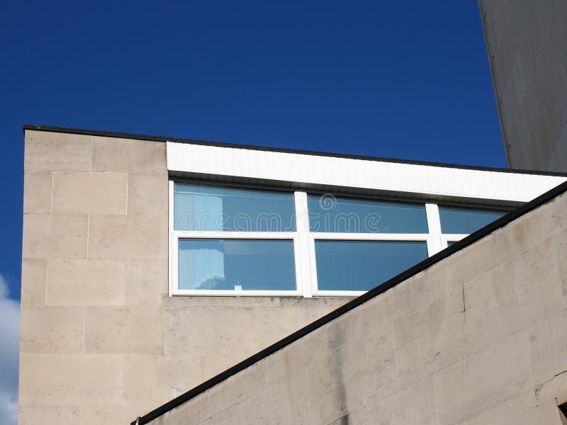 Из-за углового закрытия вид на старое здание 60-х годов, построенное из бетонного брутального красного цвета с голубым небом стоковая фотография