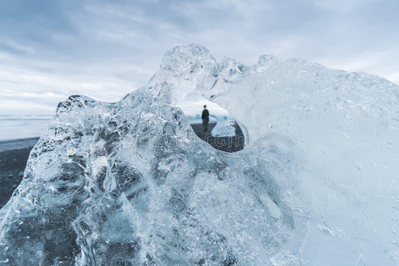 Из стоек человека фокуса самостоятельно на пляже Jokulsarlon в Исландии стоковая фотография