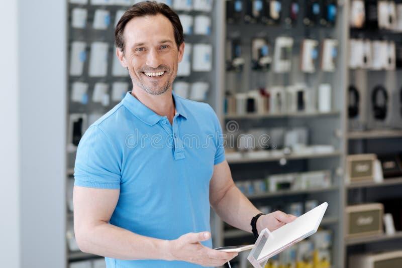 Излучающий покупатель держа умный телефон и усмехаясь в камеру стоковая фотография rf