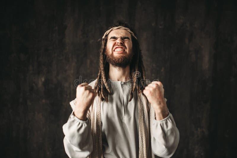 Иисус Христос в белой робе эмоционально молит стоковое изображение rf
