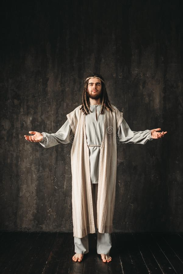 Иисус Христос моля с открытыми оружиями стоковые фото