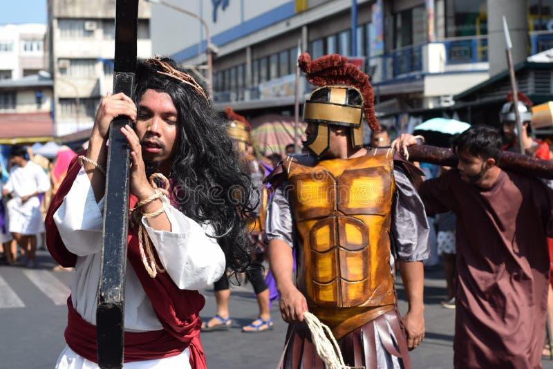 Иисус Христос нося толпу деревянного перекрестного admist веселя, драму улицы представляя события это привело к его распятию стоковые изображения rf