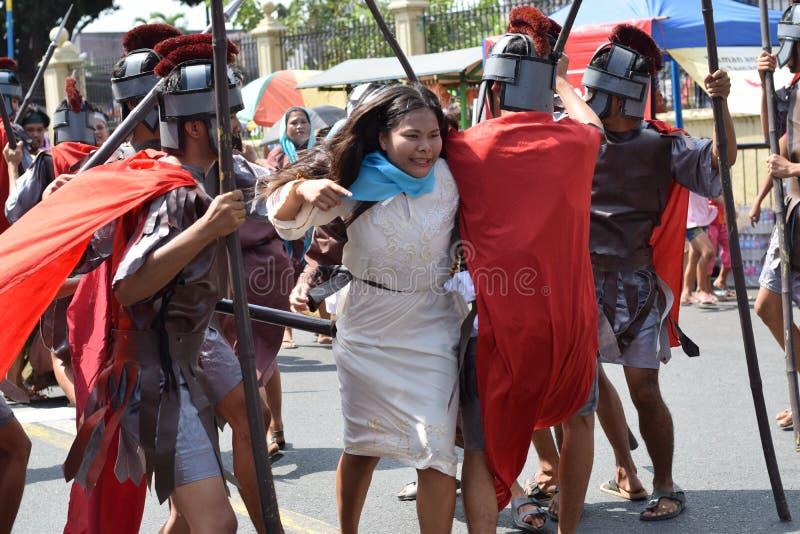 Иисус Христос яростного бега женщины атакуя, драма улицы, община празднует страстную пятницу представляя события это привело к c стоковая фотография rf