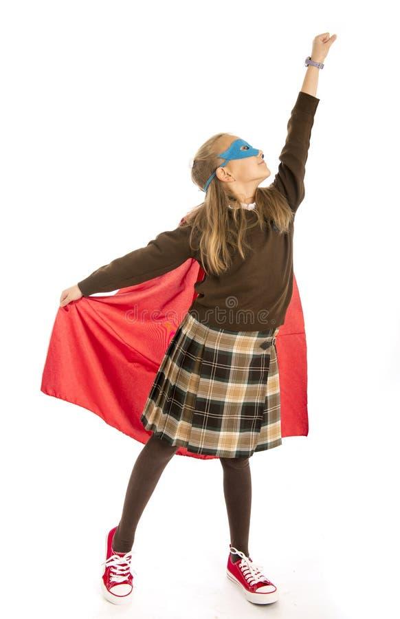 7 или 8 лет старой молодой девочки в костюме супергероя над выполнять школьной формы счастливый и excited изолированном на задней стоковое фото
