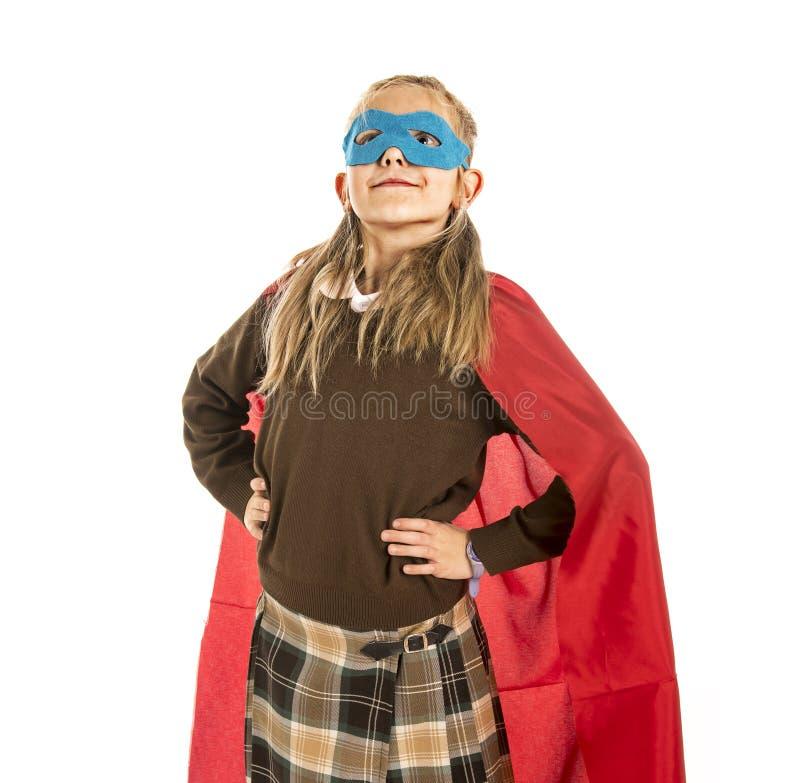 7 или 8 лет старой молодой девочки в костюме супергероя над выполнять школьной формы счастливый и excited изолированном на задней стоковые изображения