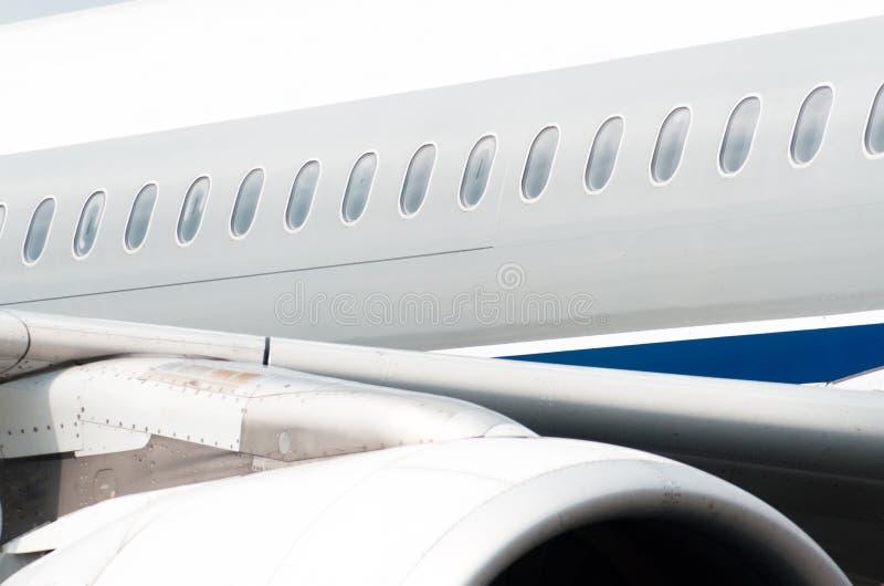 Иллюминаторы самолета на фюзеляже, взгляд над двигателем и крыло стоковые фото