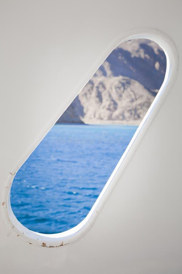 Иллюминатор на палубе обозревая море и горы стоковые фото