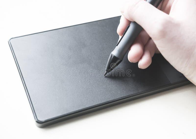 Иллюстратор на работе с ручкой и таблеткой стоковое фото